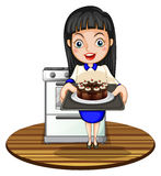 Une fille faisant un gâteau cuire au four Image stock