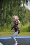 Une fille fait sauter sur l'attraction sautante photographie stock