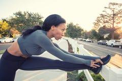 Une fille foncée sportive de peau étirant sa jambe sur une barrière dans le pair Photographie stock libre de droits