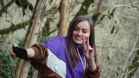 Une fille heureuse dans un olympium pourpre fait une paix-selfie des arbres couverts de mousse dans une forêt brumeuse de buis banque de vidéos
