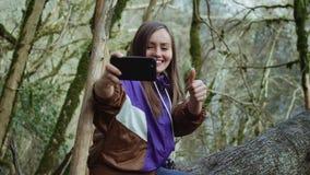 Une fille heureuse dans un olympium pourpre montre comme et fait le selfie sur le fond des arbres couverts de mousse banque de vidéos