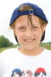 Une fille heureuse dans une casquette de baseball vers l'arrière bleue. Photos stock