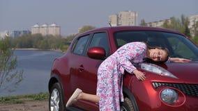 Une fille heureuse la déplace pour remettre le corps d'une nouvelle voiture, fixant sur le capot et étreignant la voiture 4K MOIS banque de vidéos