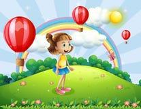 Une fille heureuse observant les ballons à air Photographie stock