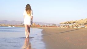Une fille heureuse va sur la mer dans une chemise blanche HD banque de vidéos