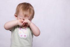 Une fille infantile essuient loin les larmes Photo stock