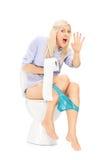 Une fille interrompue s'asseyant sur une toilette Images libres de droits