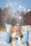 Une fille jette la neige sur une promenade Appréciez l'hiver neigeux photos libres de droits