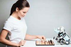 Une fille joue avec un robot dans les échecs Le robot se repose vis-à-vis de elle sur la table Photos libres de droits