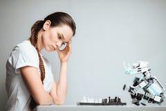 Une fille joue avec un robot dans les échecs Le robot se repose vis-à-vis de elle sur la table Images libres de droits