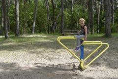 Une fille joue sur le terrain de jeu sur l'attraction en métal jaune Il est venteux photos stock