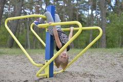 Une fille joue sur le terrain de jeu sur l'attraction en métal jaune Il est venteux images libres de droits