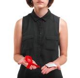 Une fille jugeant un préservatif et un ruban rouge d'isolement sur un fond blanc Service de santé Concept de propagande de sexe s Images stock