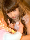Une fille jure à une poupée Photo stock