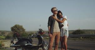 Une fille latine et un jeune garçon blond se tiennent sur la route près de leur rétro motocyclette et regardent dans la distance banque de vidéos
