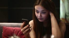 Une fille le soir dans un café utilisant le smartphone banque de vidéos