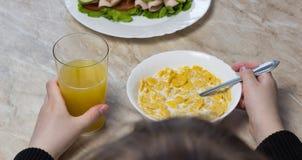 Une fille mange des cornflakes avec du lait devant l'écolière d'école images stock