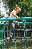 Une fille marchant sur l'échelle à la cour de jeu Image stock