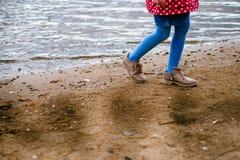 Une fille marche le long de l'eau Image libre de droits