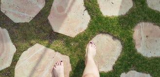 Une fille marche nu-pieds sur le chemin rond de pierres dans l'herbe image stock