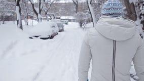 Une fille marche sur la route pendant le jour d'hiver, toute dans la neige, vue du dos banque de vidéos