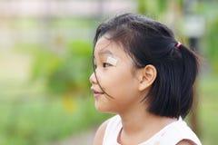 Une fille mignonne regardant quelque chose et sa blessure la fin de l'e photographie stock