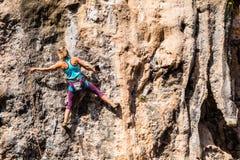 Une fille monte une roche photos stock