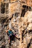 Une fille monte une roche photographie stock libre de droits
