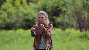 Une fille montre son ami du doigt se tenant sur un beau pré banque de vidéos