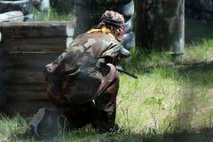 Une fille pendant un jeu de paintball sur la décharge Camouflez le costume, le masque protecteur, l'écharpe de cou jaune et les a photo stock