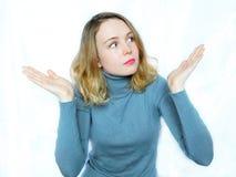 Une fille perplexe gesticule Photographie stock