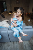 Une fille plus âgée et plus jeune sur le grand divan Image stock