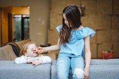 Une fille plus âgée et plus jeune sur le grand divan Photo stock