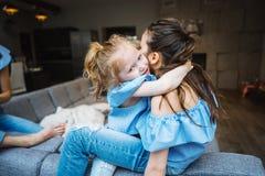 Une fille plus âgée et plus jeune sur le grand divan Photographie stock libre de droits