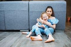 Une fille plus âgée et plus jeune sur le plancher Image stock