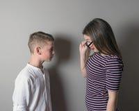 Une fille plus âgée grondant un plus jeune garçon sur le fond gris photos stock