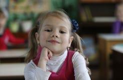 Une fille préscolaire s'assied à un bureau photos stock