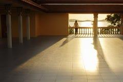 Une fille prend des photos de son amie contre le coucher du soleil dans un temple bouddhiste Image libre de droits