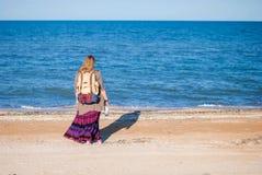 Une fille recule et regarde la mer La fille hippie regarde la mer La femme avec une bouteille de vin est par la mer hippie Image libre de droits