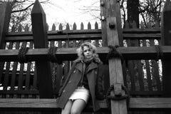 Une fille restant près des bâtons en bois Photographie stock libre de droits