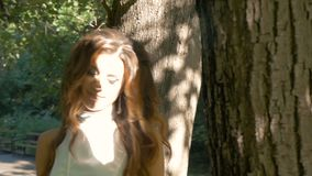 Une fille romantique marche en parc banque de vidéos