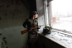Une fille rousse mince se tient ? la fen?tre cass?e avec un fusil La fille dans le camouflage vert avec une arme ? feu Service mi images libres de droits