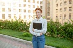 Une fille rousse triste avec des taches de rousseur sur son visage tient un dossier dans des ses mains image stock