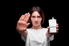 Une fille sérieuse avec un paquet de cigarettes sur un fond noir Jeune femme montrant un signe d'arrêt Style de vie sain images stock