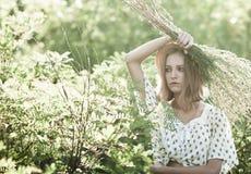 Une fille sérieuse dans un chapeau de paille protège son visage avec un groupe de haute herbe de mauvaises herbes, Photos stock