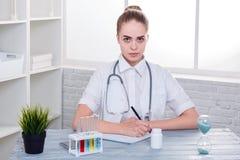 Une fille sérieuse, un docteur dans l'uniforme, s'assied à son bureau et écrit quelque chose dans un carnet indoors image libre de droits