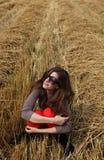 Une fille s'asseyant dans une meule de foin Images stock