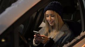 Une fille s'asseyant dans une voiture et parlant au téléphone banque de vidéos