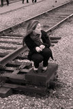 Une fille s'asseyant près du chemin de fer Photographie stock libre de droits
