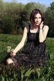 Une fille s'asseyant sur l'herbe Photo libre de droits